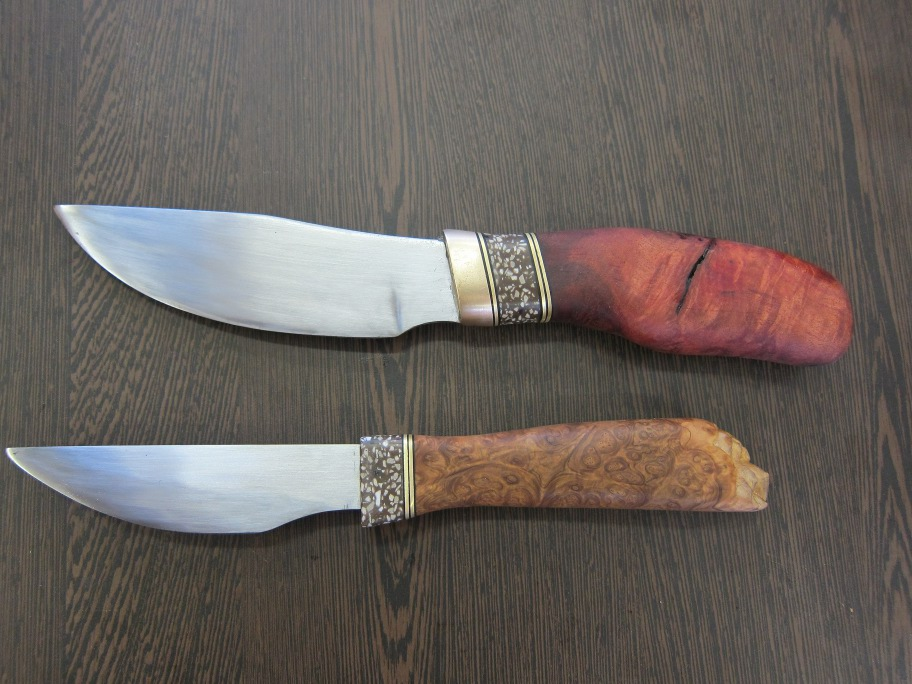 Two finished knives. Layers of brass, plastic visible on one red wood and one other wooden handle.