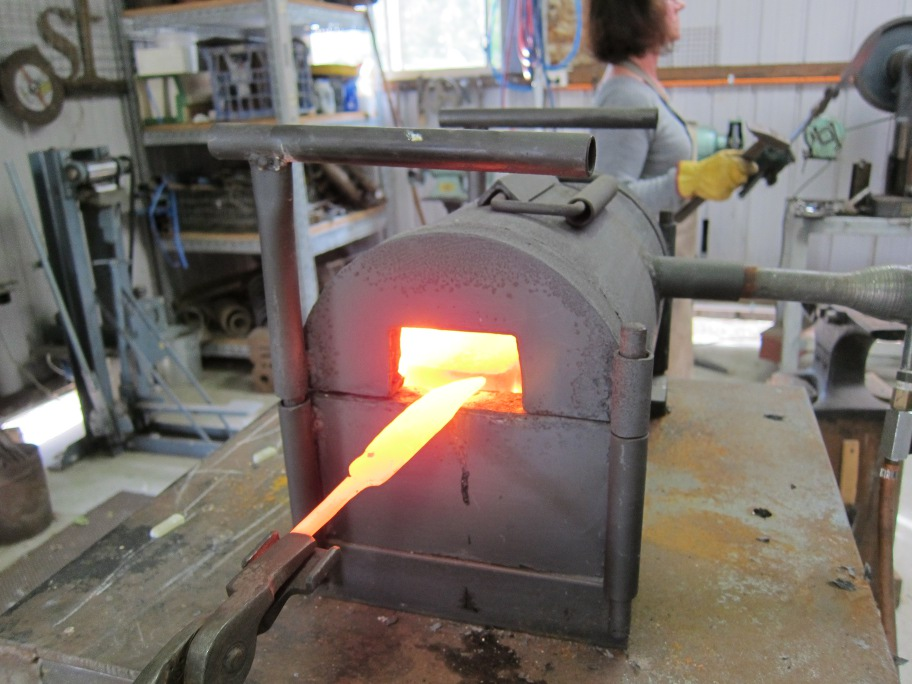 A  bright yellow bar of metal with a knife shape on one end is withdraw from the gas forge.