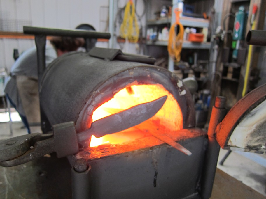 A knife shape is being heated in front of the face of the forge.