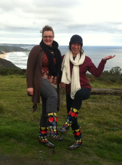 Two students showing their identical black gum boots with polka dots