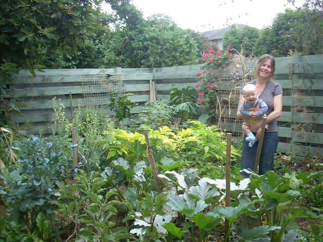 Picture of the lucious Kemp Street Garden with Bryony standing in it holding baby Lucian. Both are smiling